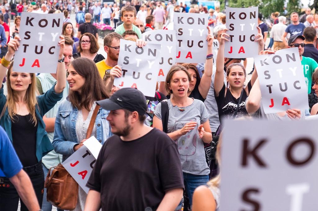 Protestujący ludzie trzymający plakat KonsTYtucJA