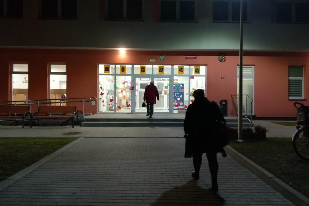 Dwie osoby wchodzą do oświetlonego budynku