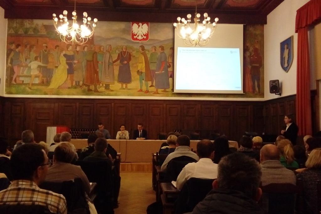 Grupa ludzi na sali sesyjnej, na ekranie prezentacja