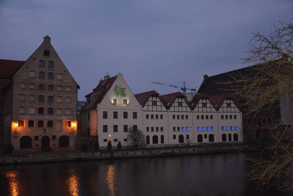 zdjęcie: z oddali widać stojący nad rzeką budynek, w którym okna zostały podświetlone na niebiesko
