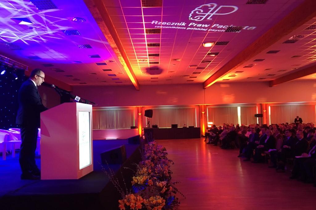 Mężczyzna przemawia w sali konferencyjnej oświetlonej czerwonymi i fioletowymi światłami