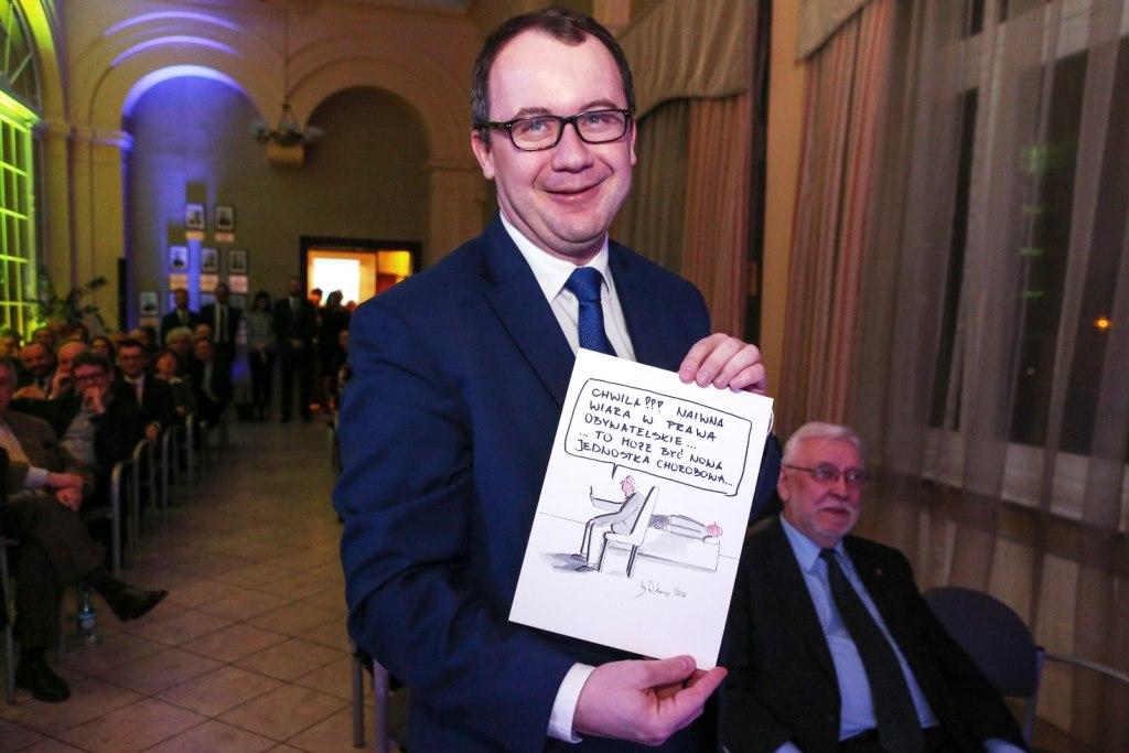 Uśmiechnięty Adam Bodnar trzyma rysunek satyryczny, na którym lekarz bada pacjenta.