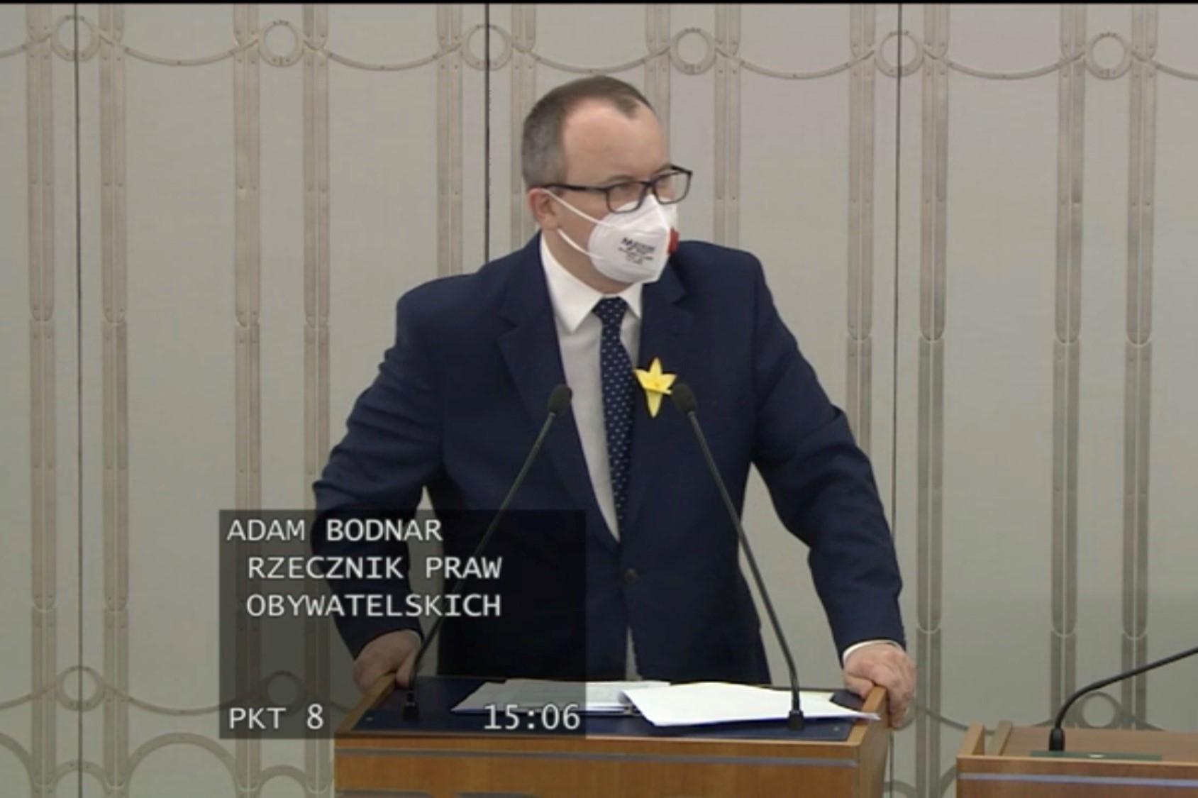 mężczyzna w maseczce przemawia za mównicą