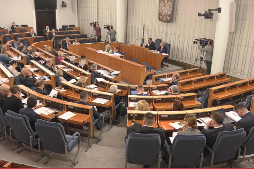 Osoby  siedzą w sali i dyskutują