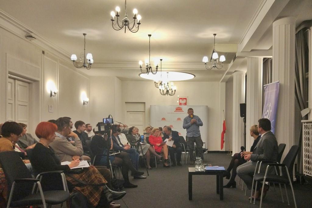 Ludzie na sali rozmawiają. Stojący mężczyzna zadaje pytanie