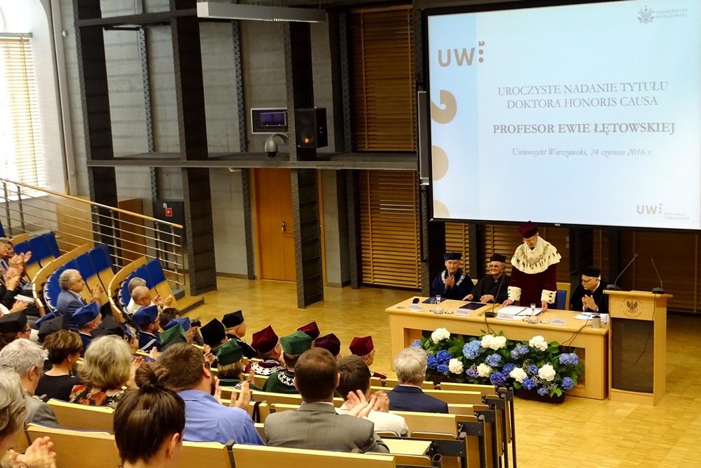 zdjęcie: na auli wykładowej siedzą ludzie, w centrum stali jest stół konferencyjny za ktorym są czteryy osoby w togach, jedna z nich stoi