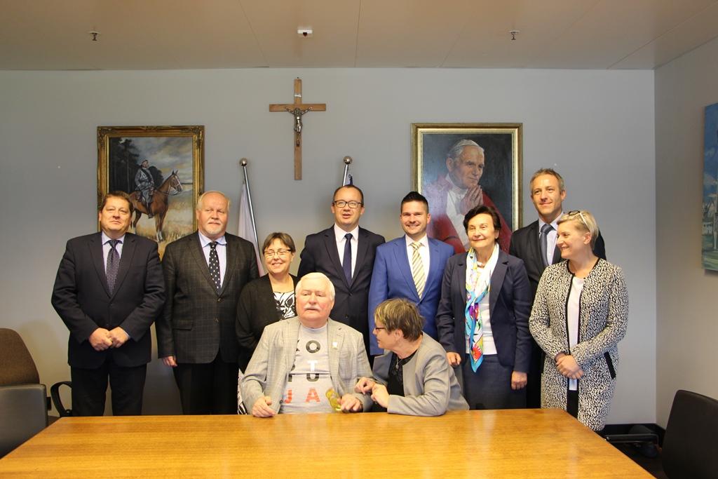 Zdjęcie grupowe. Mężczyzna w koszulce z napisem KonsTYtucJA otoczony przez gości. W tle: krzyż, portret papieża Jana Pawła II i portret marszałka Piłsudskiego