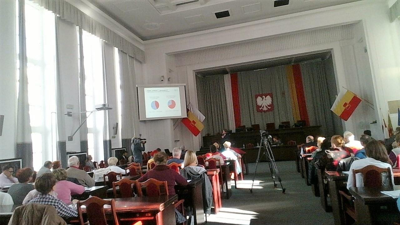 Ludzie siedzą  na sali obrad władz samorządowych. Flagi Łodzi