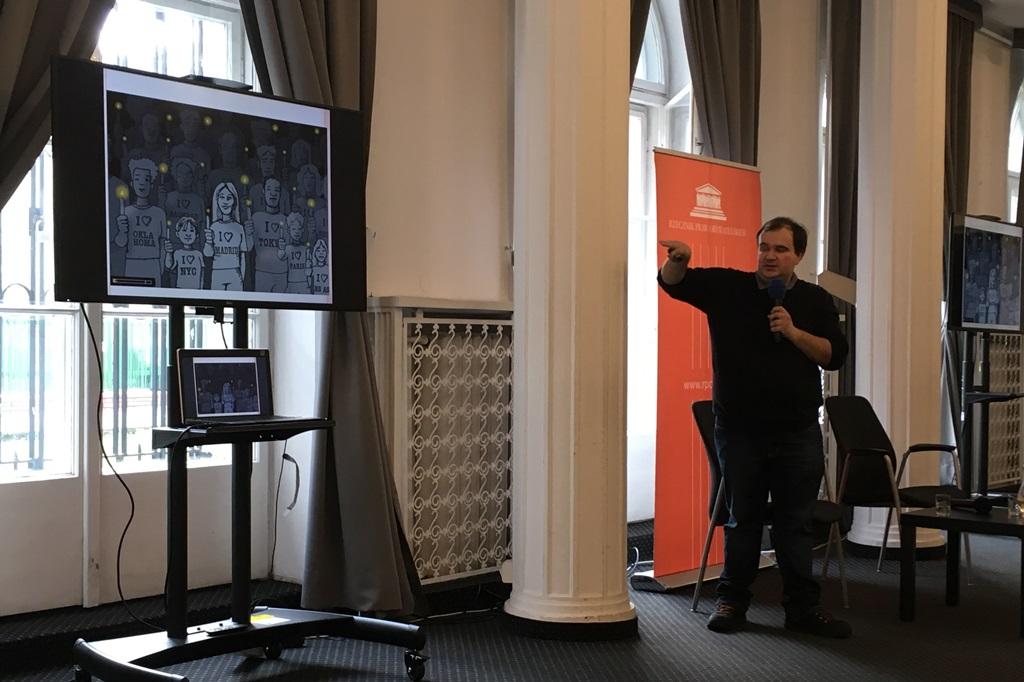 Mężczyzna pokazuje na ekran z grą