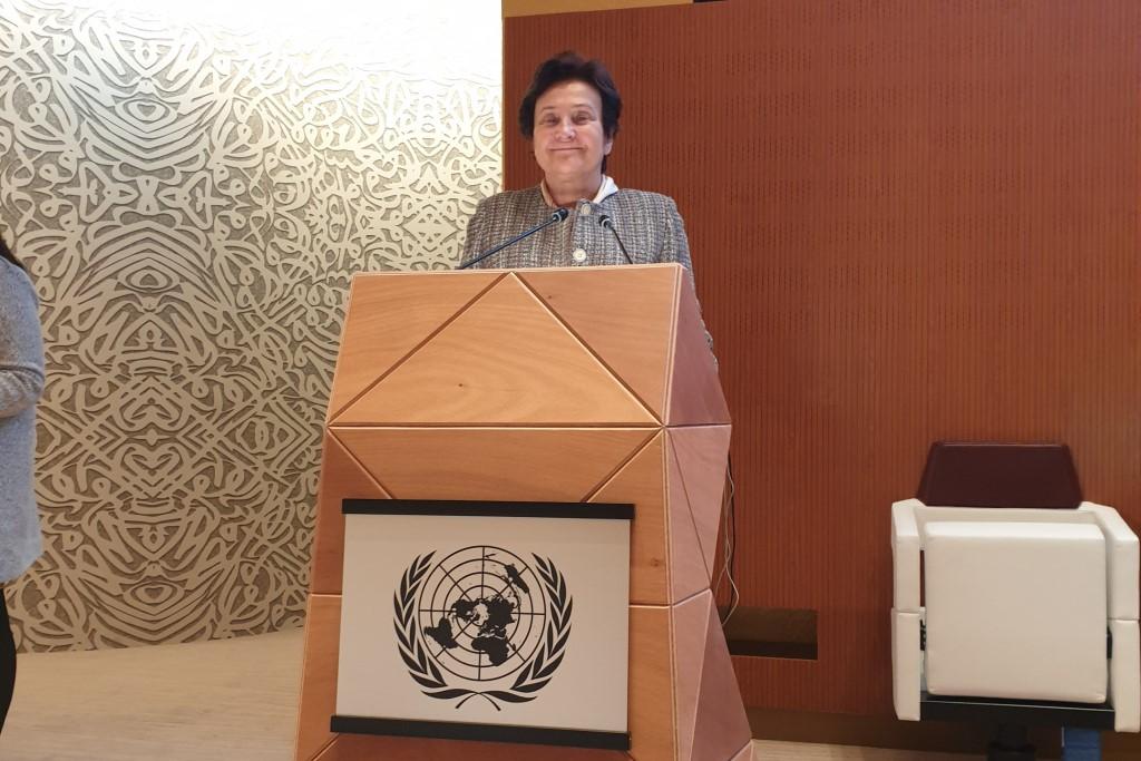 Kobieta przy mównicy ze znakiem kontynentów na mapie - logiem ONZ