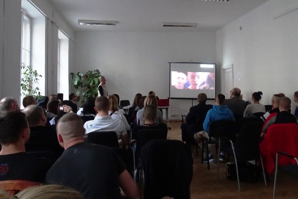 Zdjęcie: uczestnicy spotkania w ujęciu od tyłu, w głebi ekran