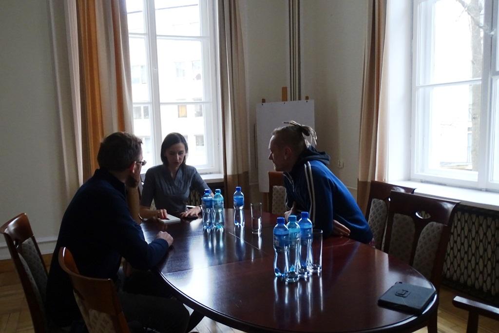 Zdjęcie: dwaj mezczyźni i kobieta rozmawiają przy stole