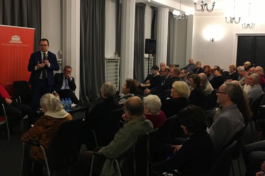 Zdjęcie: sala pełna siedzących ludzi, a mężczyzna stoi. W tle pomarańczowe logo RPO