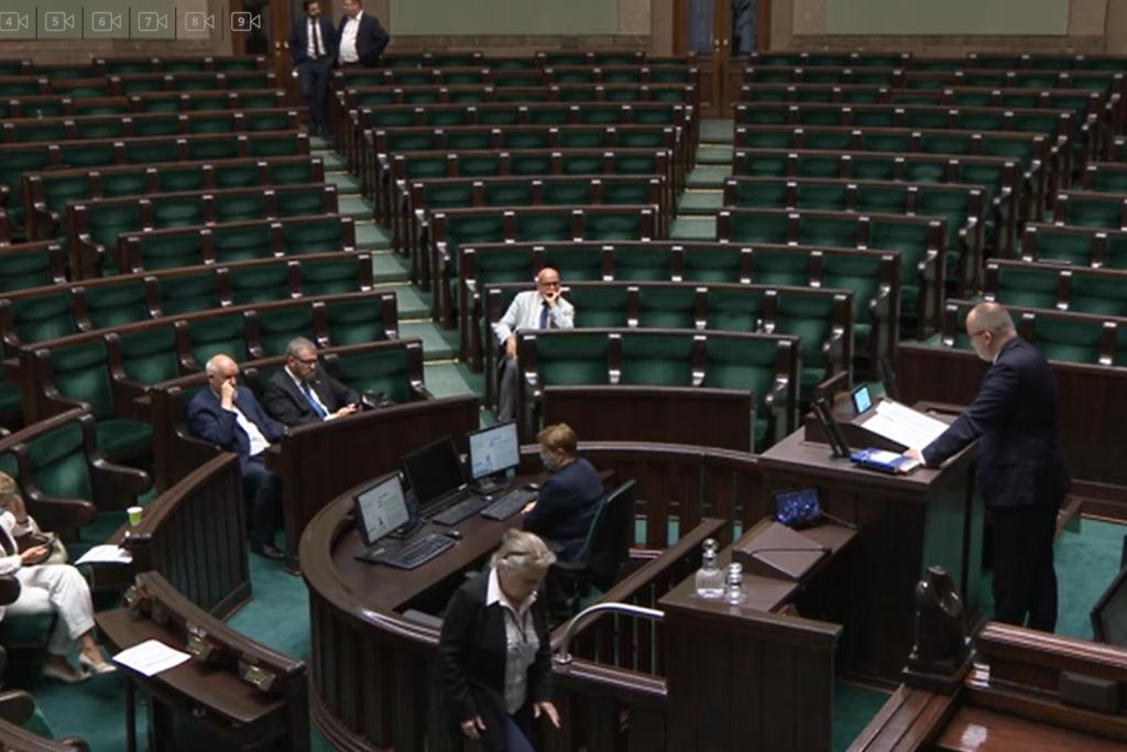 Mężczyzna na mówinicy w Sejmie. Puste ławy po prawej stronie
