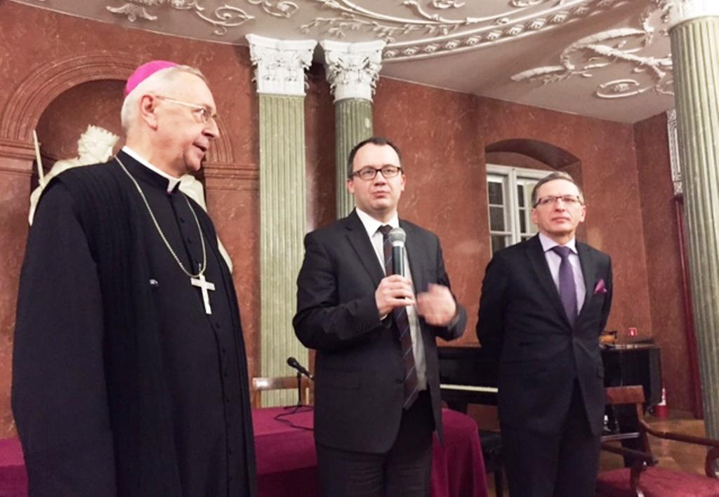 Biskup i dwaj mężczyźni w garniturach w zabytkowej sali