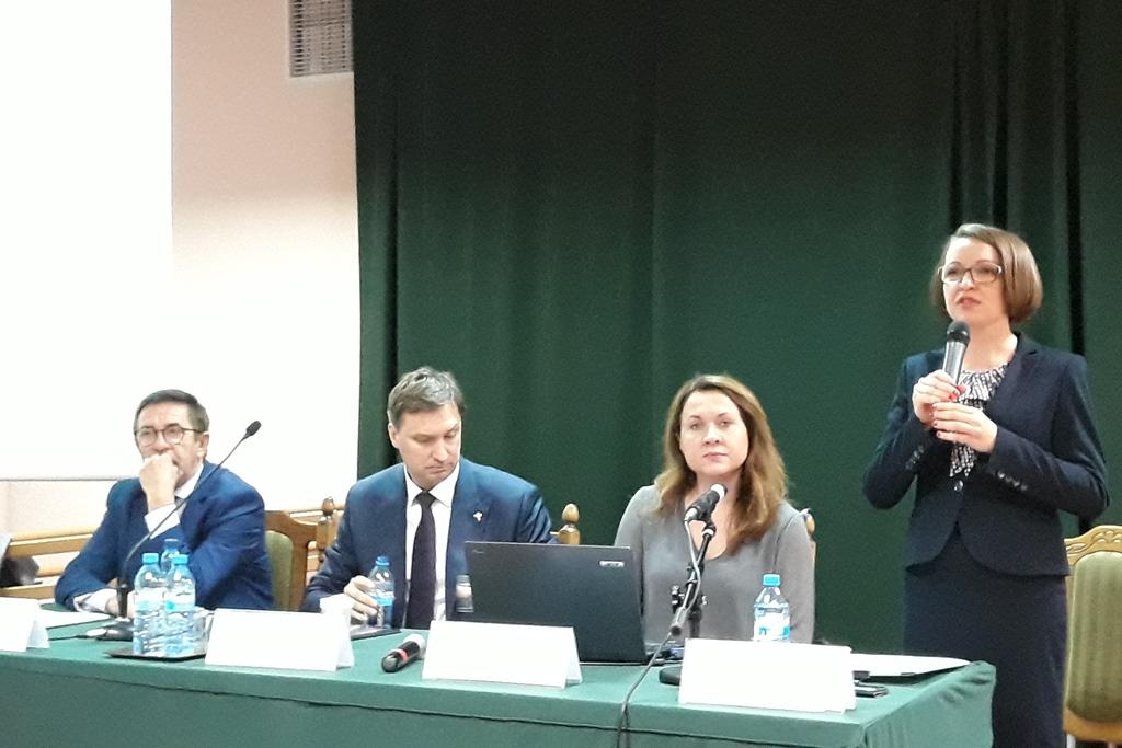 Dwóch mężczyzn i kobieta za stołem panelowym, druga kobieta stoi z mikrofonem