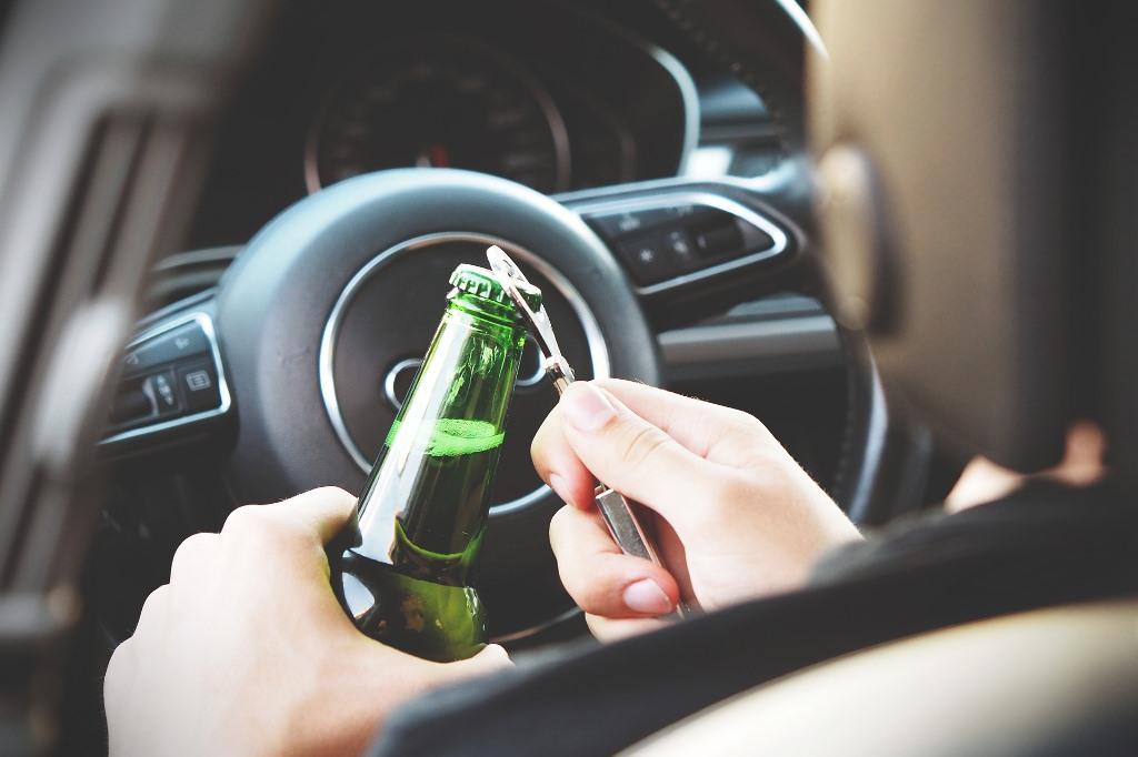 Człowiek za kierownicą otwiera zakapslowaną butelkę