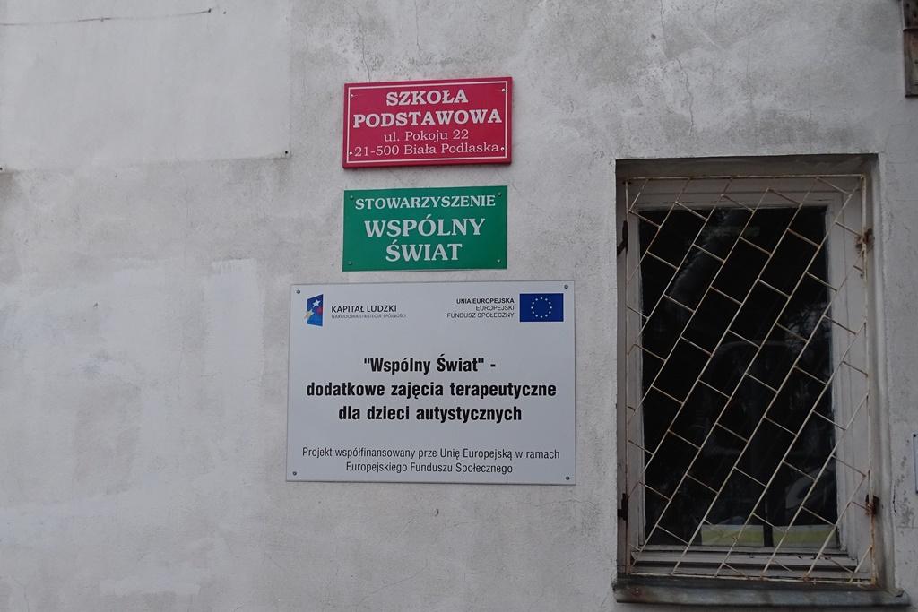"""Tablica na scianie """"Stowarzyszenie WSPÓLNY ŚWIAT"""", """"Szkoła Podstawowa"""""""