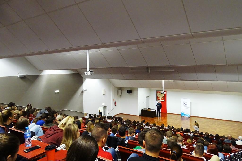Aula wykładowa pełna słuchaczy, mezczyzna na scenie