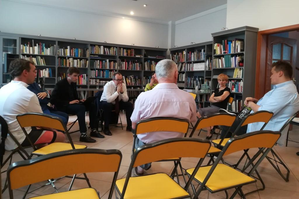 Grupka ludzi w bibliotece. Mężczyzna w białej koszuli słucha
