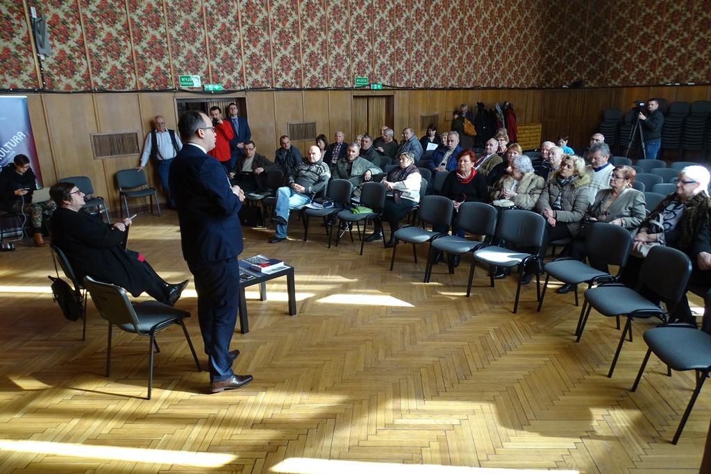 Ludzie na sali widowiskowej domu kultur, mężczyzna mówi na stojąco