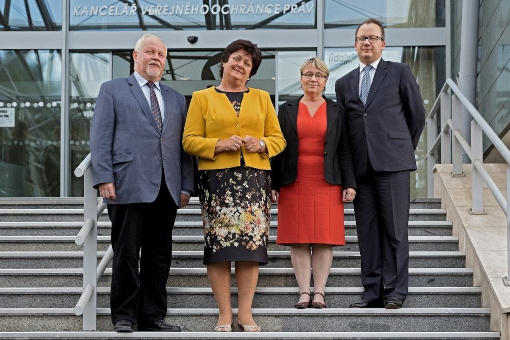 Cztery osobby pozują do zdjęcia na schodach przed budynkiem