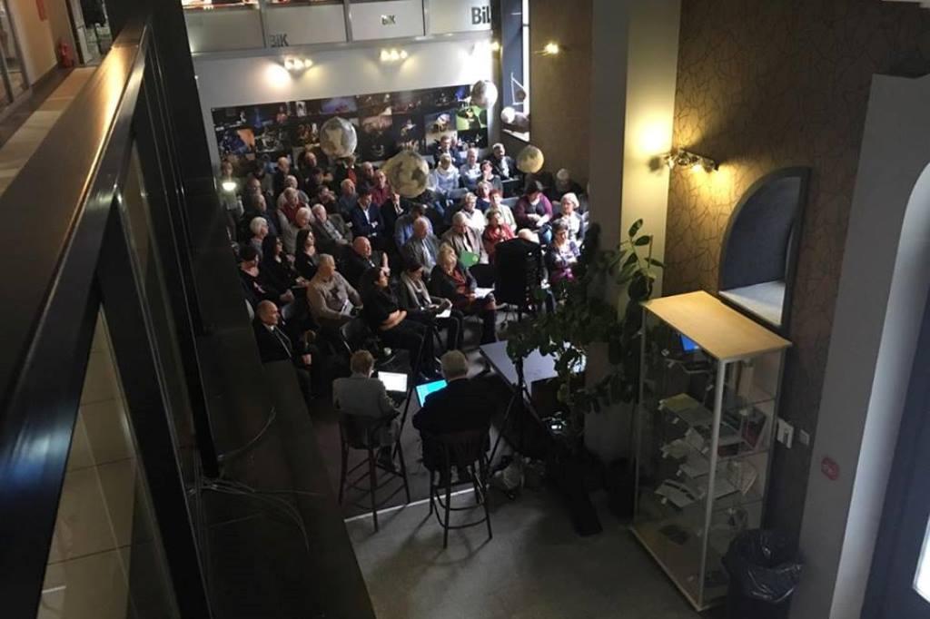 Zdjęcie: widok z antresoli na salę z ludżmi siedzącymi na krzesłach