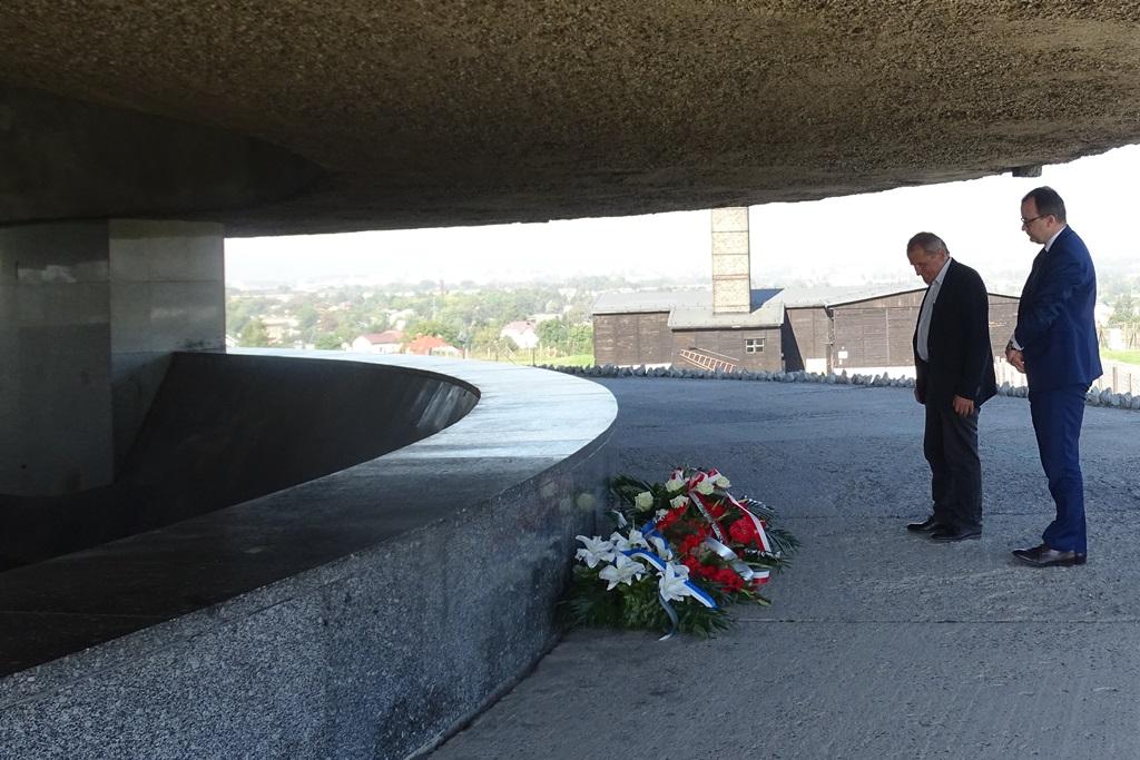 Zdjęcie: dwaj mężczyźni przed betonowym pomnikiem