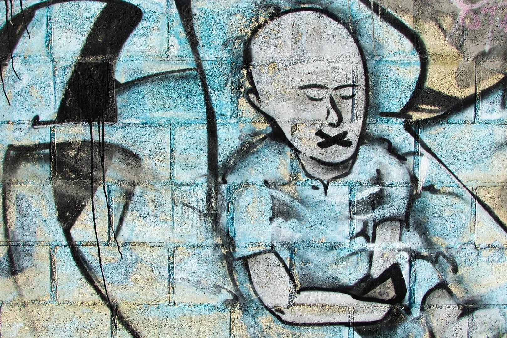 Graffiti z mężczyzną z zaklejonymi ustami