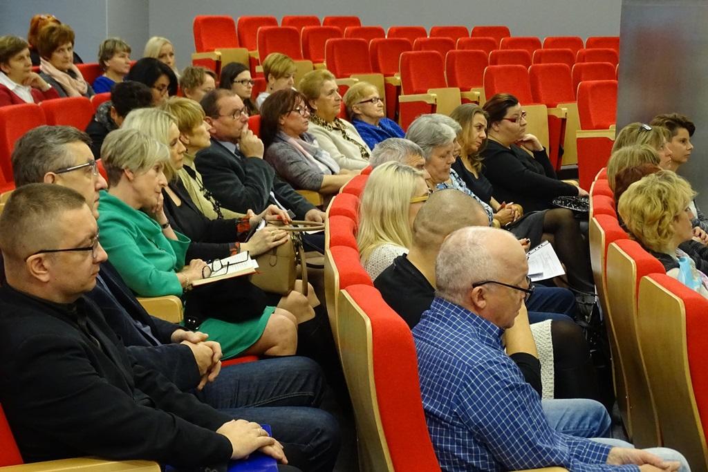 Zdjęcie: ludzie siedzą na czerwonych fotelach w sali audytoryjnej. Ujęcie z boku