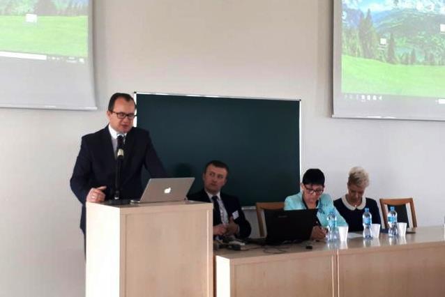 zdjęcie: mężczyzna w garniturze stoi przy mównicy, obok niego siedzi kilka osób