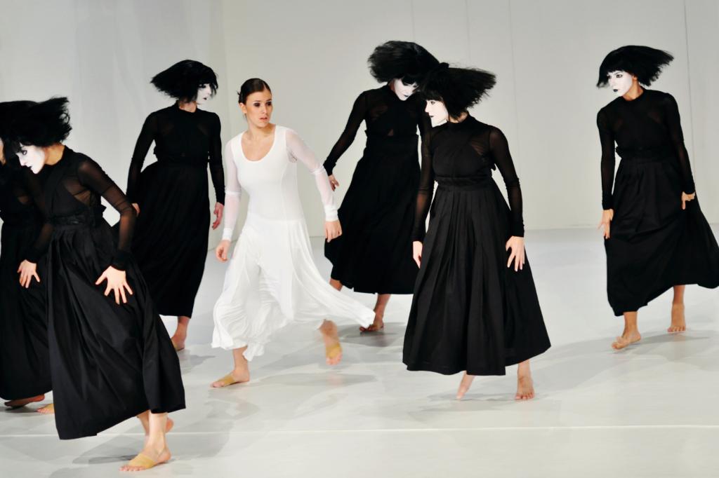 Tancerki w czarnych strojach i białych maskach. Jedna w białym stroju i bez maski