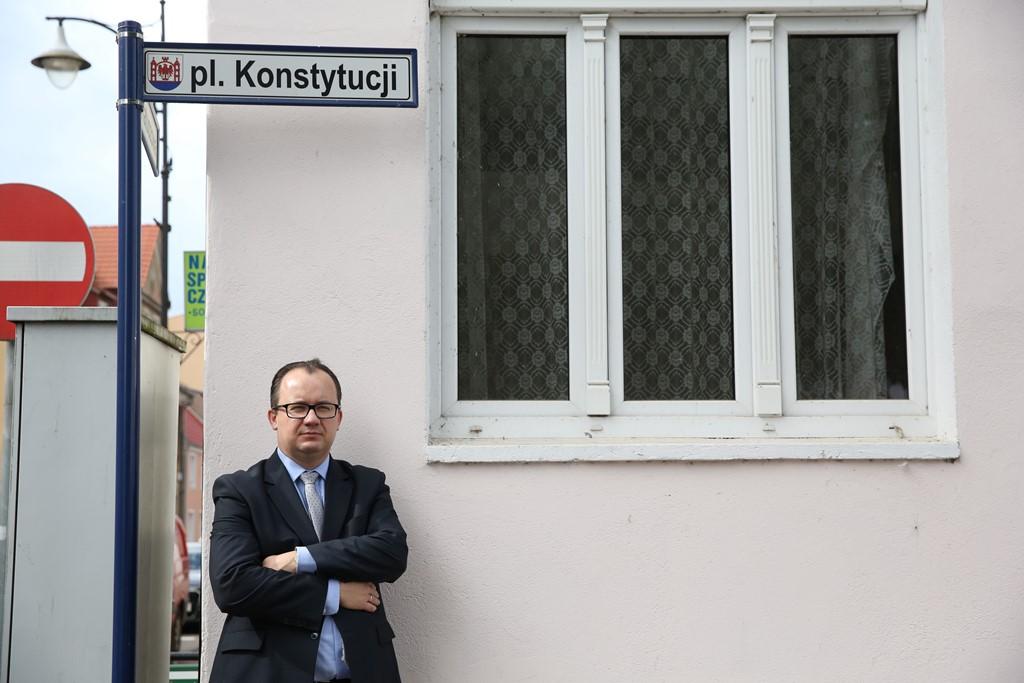 """Mężczyzna pod domem z nampisem """"Plac Konstytucji"""""""