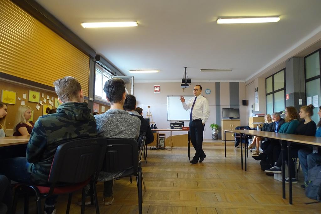 Mężczyzna bez marynarki mówi do uczniów