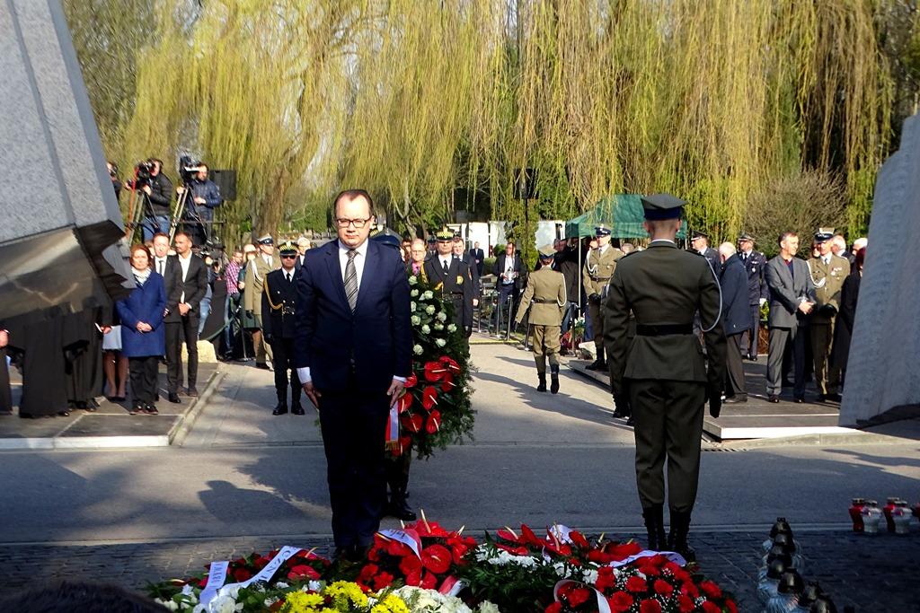 Mężczyzna stoi przed pomnikiem z pochyloną głową