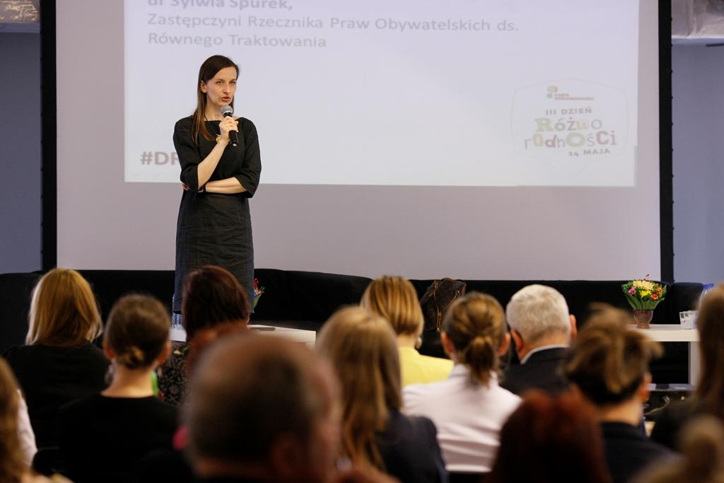 zdjęcie: kobieta w ciemnej sukience stoi na scenie i przemawia do siedzących naprzeciw niej osób