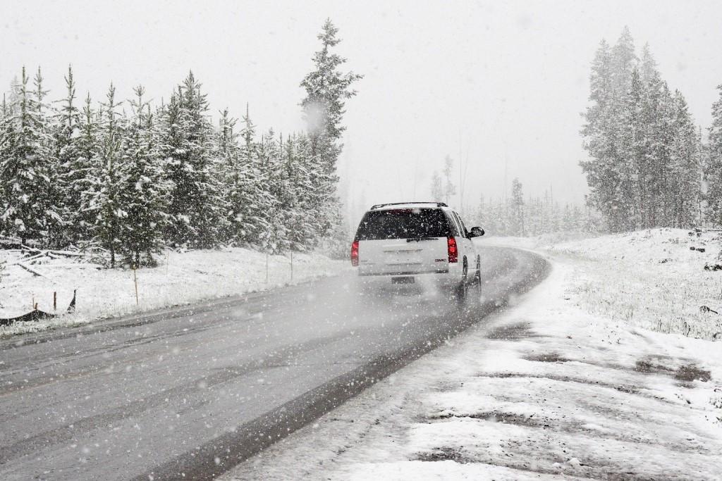 Samochód jedzie zaśnieżoną drogą przez las