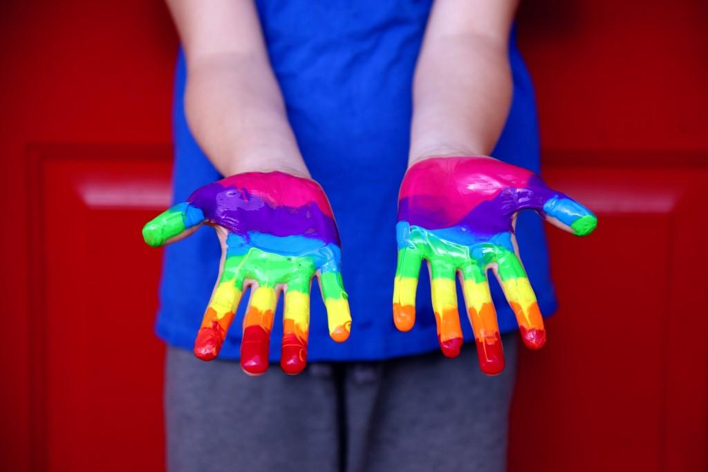 Dłonie bawiącego się dziecka pomalowane farbką w kolorach tęczy