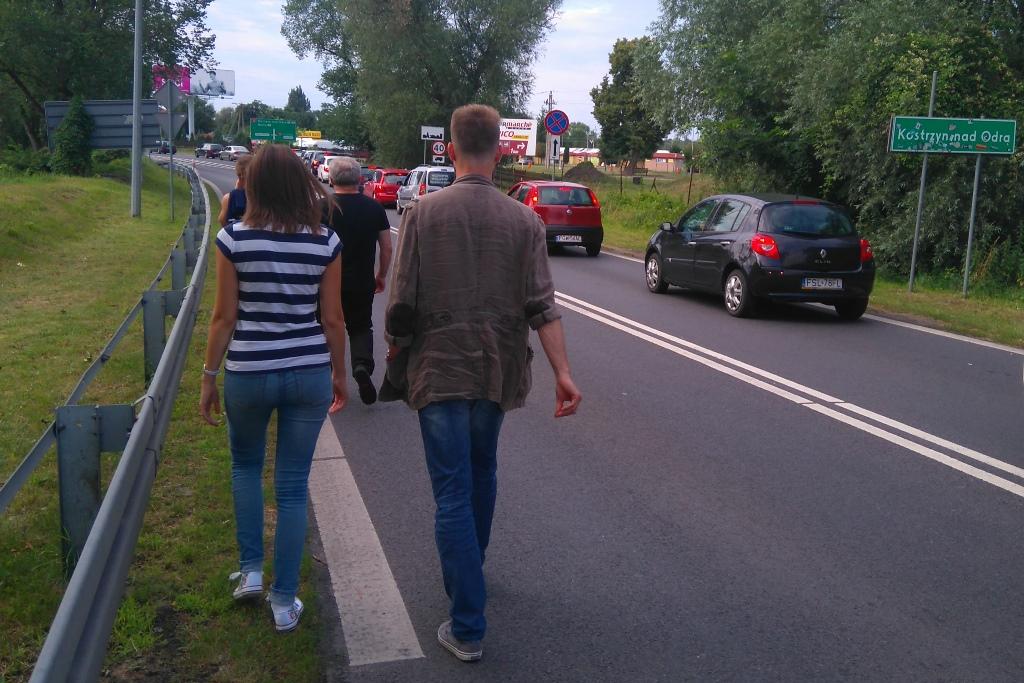 Zdjęcie: grupa ludzi idzie poboczem drogi, widać tablicę Kostrzyń nad Odrą.