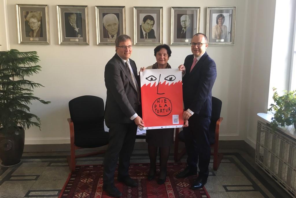 """Dwaj mężczyźni i kobieta trzymają bialo-czerwony plakat z napisem """"Nie dla tortur"""""""