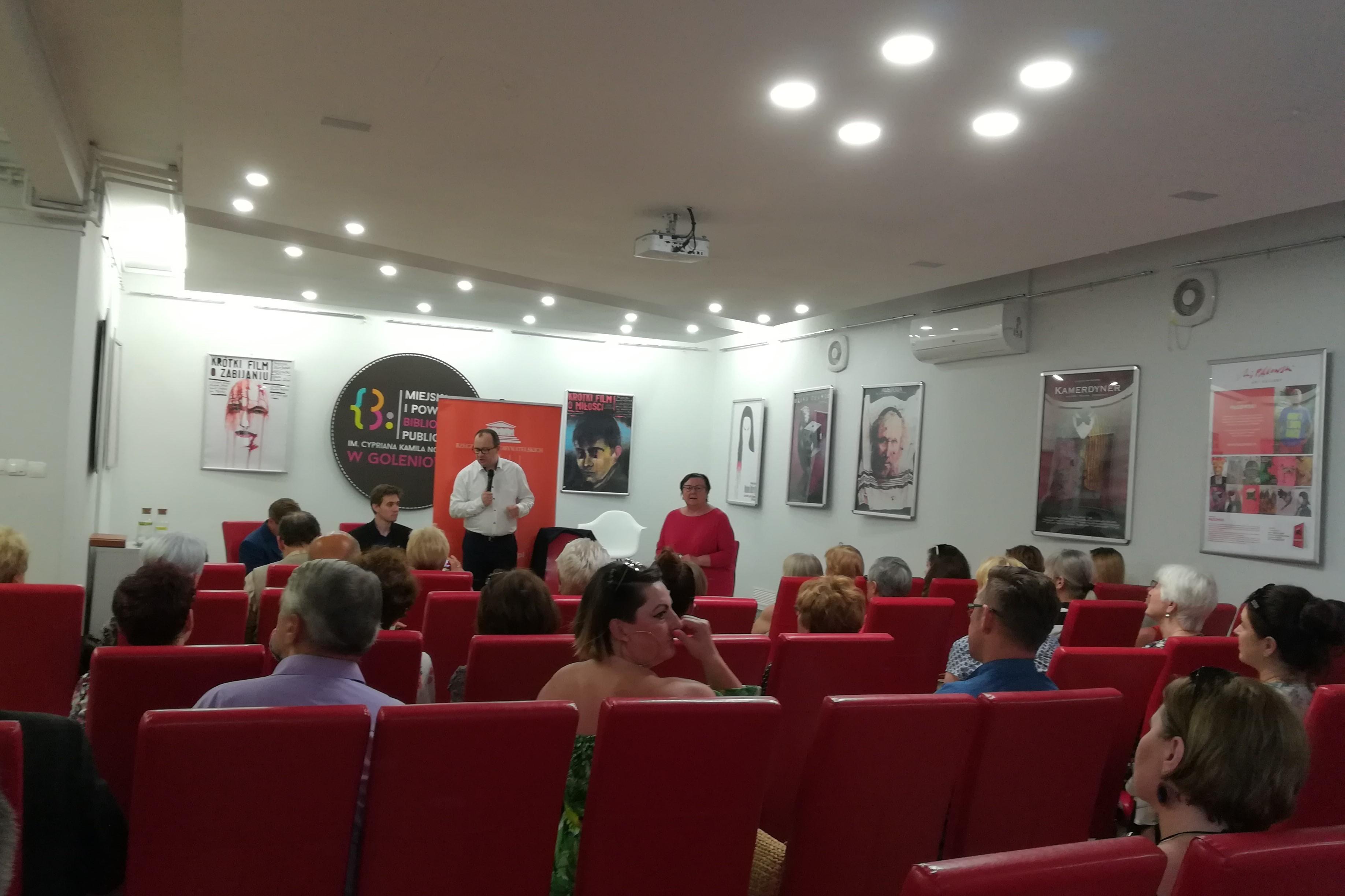 Ludzie na sali, czerwone krzesła