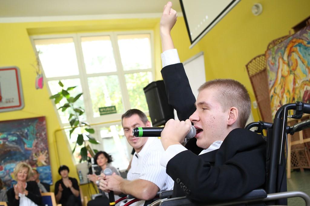 Młody mężczyzna na wózku śpiewa i podnosi rękę