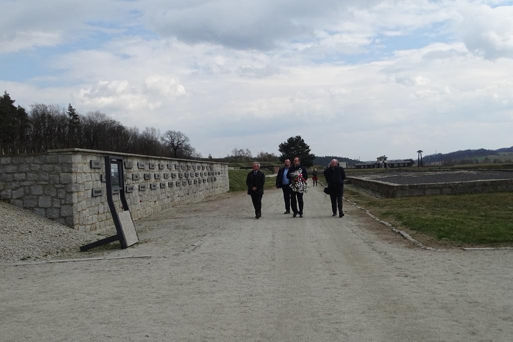 Grupa ludzi z kwiatami na terenie obozu koncentracyjnego