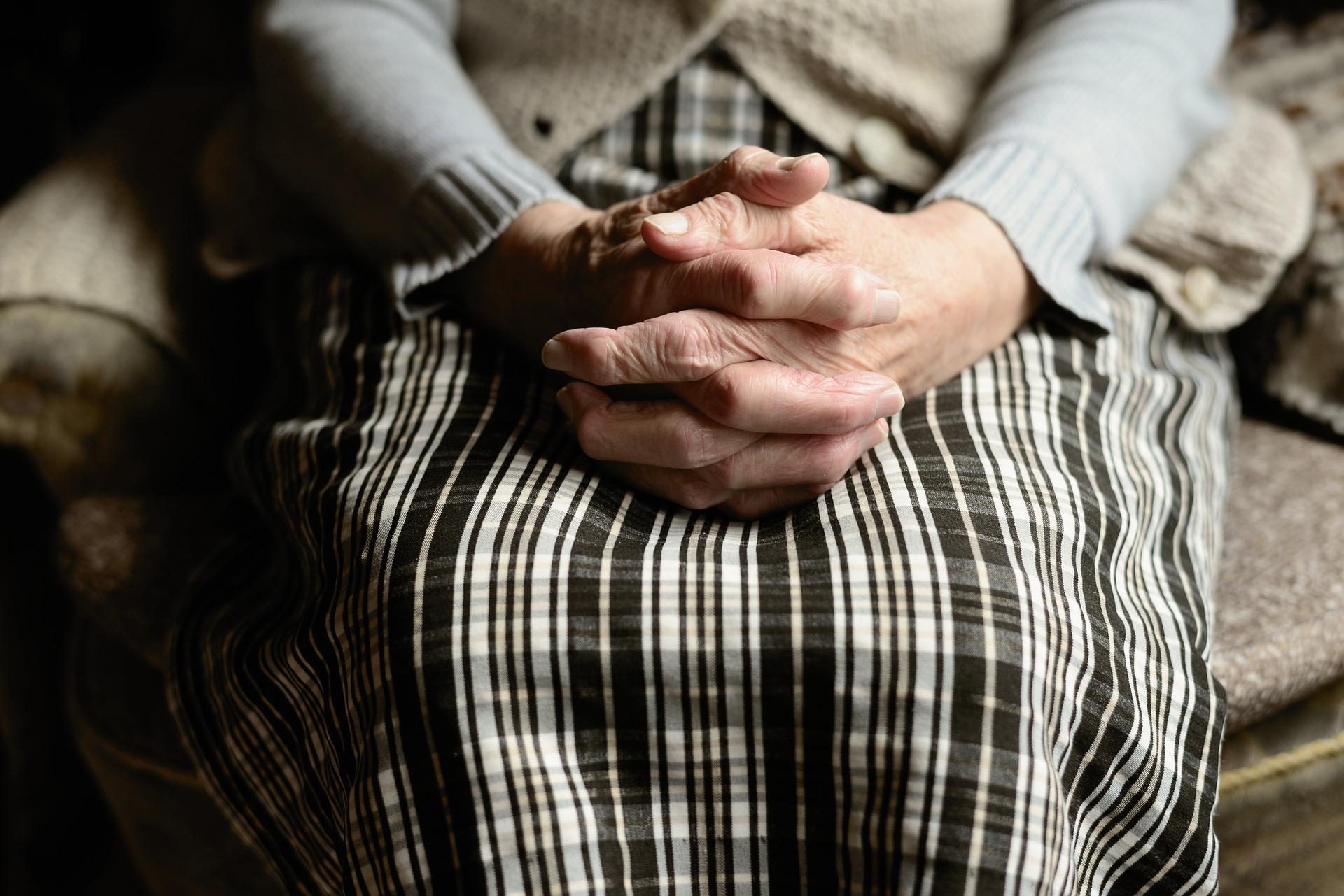 Ręce starszej osoby splecione na podołku