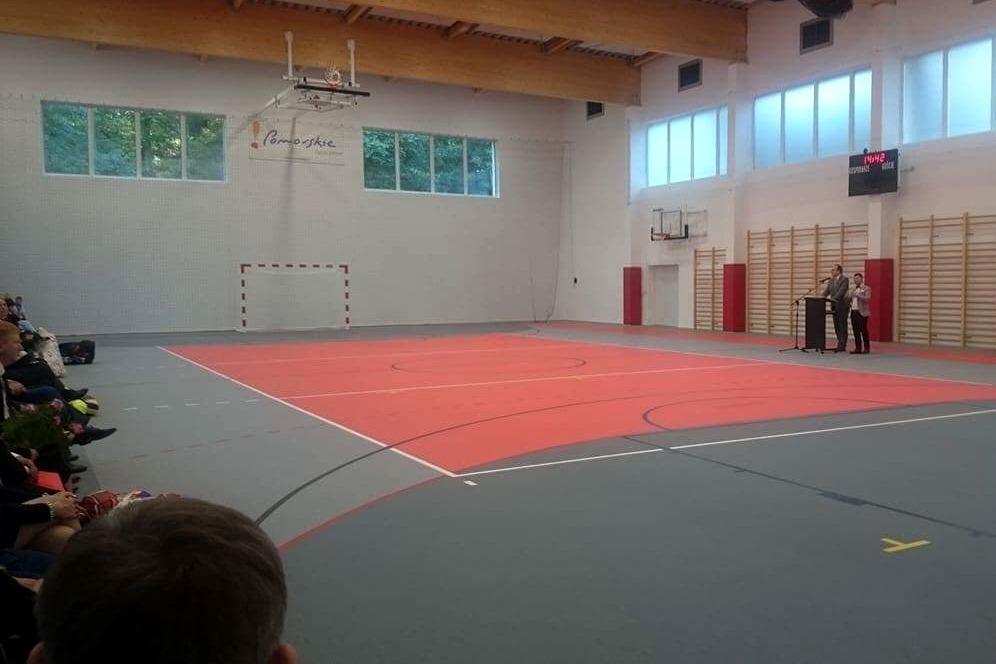 zdjęcie: mężczyzna stoi przy mównicy umieszczonej na środku sali gimnastycznej
