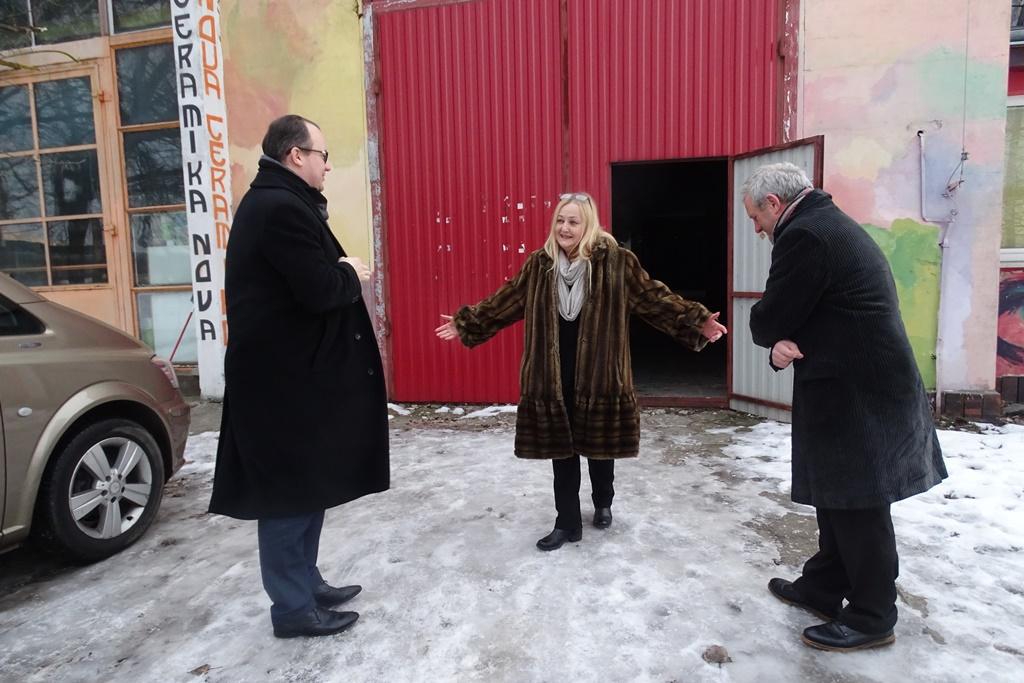 Kobieta wita dwóch mężczyzn przed halą fabryczną