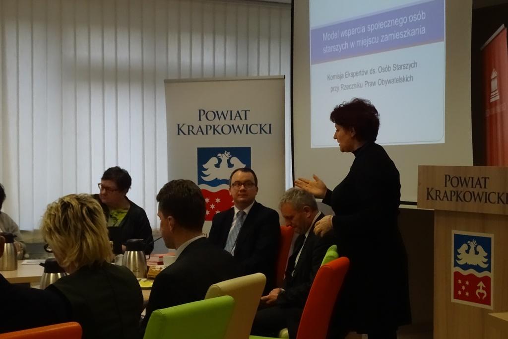 """Ludzie w nowoczesnej sali konferencyjnej, kobieta przy mikrofonie, napis """"Powiat Krapkowicki"""""""