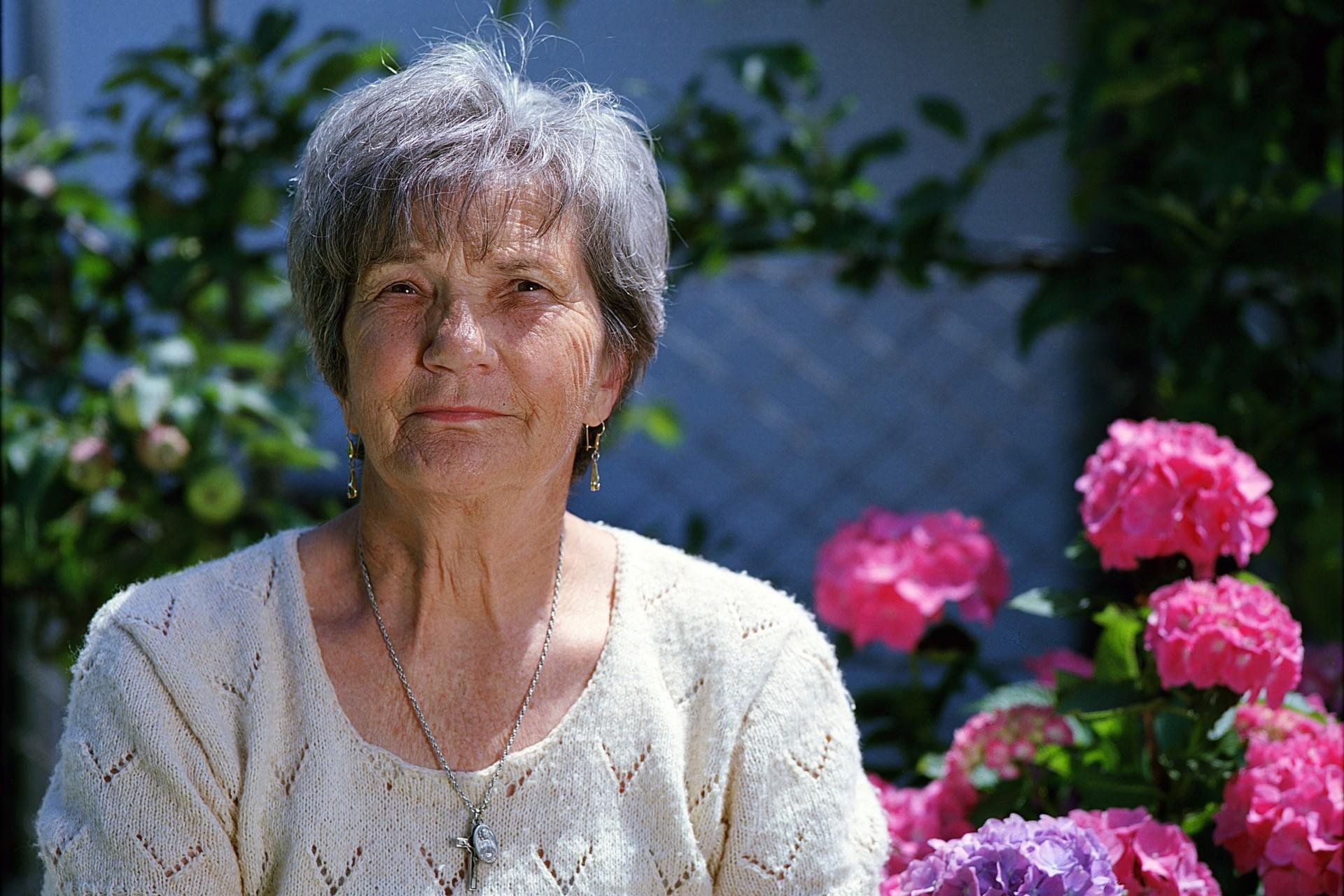 Kobieta po 60-tce, z tyłu kwiaty