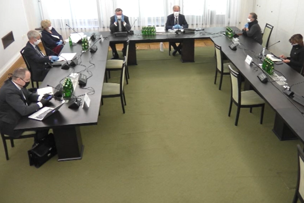 Ludzie na sali posiedzeń komisji siedzą w rozproszeniu z maseczkami na twarzach