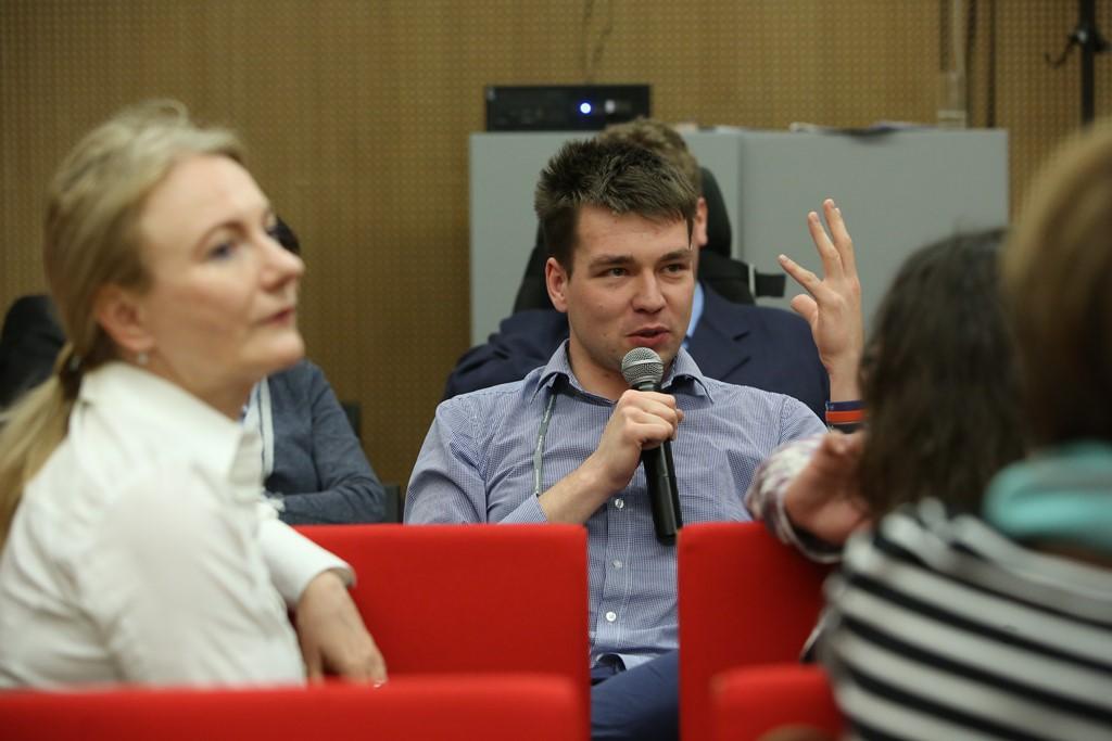 zdjęcie: mężczyzna siedzi na krzesle, mówi do mikrofonu i gestykuluje